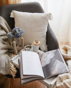 Cozy looking chair with pillow and blanket.