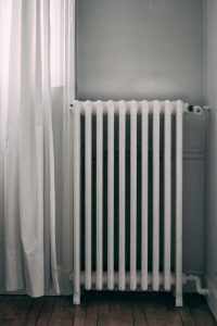 CLassic looking radiator next to a window.